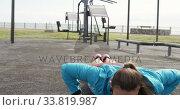 Купить «Sporty Caucasian woman exercising in an outdoor gym during daytime», видеоролик № 33819987, снято 8 августа 2019 г. (c) Wavebreak Media / Фотобанк Лори