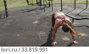 Купить «Sporty Caucasian woman exercising in an outdoor gym during daytime», видеоролик № 33819991, снято 8 августа 2019 г. (c) Wavebreak Media / Фотобанк Лори