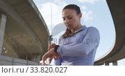 Купить «Sporty Caucasian woman checking her smartwatch outdoor», видеоролик № 33820027, снято 8 августа 2019 г. (c) Wavebreak Media / Фотобанк Лори