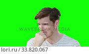 Купить «Worried Caucasian man on green background», видеоролик № 33820067, снято 8 августа 2017 г. (c) Wavebreak Media / Фотобанк Лори