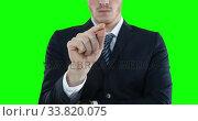 Купить «Mid section of a Caucasian man raising hand on green background», видеоролик № 33820075, снято 8 августа 2017 г. (c) Wavebreak Media / Фотобанк Лори