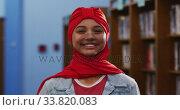 Купить «Portrait of a smiling Asian female student wearing a red hijab and looking at camera», видеоролик № 33820083, снято 7 июня 2019 г. (c) Wavebreak Media / Фотобанк Лори