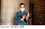Купить «Stylish female wearing face mask standing on staircase in building and putting on disposable latex gloves before city stroll during coronavirus epidemic», видеоролик № 33827095, снято 14 мая 2020 г. (c) Ekaterina Demidova / Фотобанк Лори
