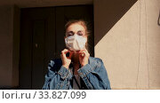 Купить «Female in trendy wear standing on street in medical mask during quarantine and putting on eyeglasses while looking at camera», видеоролик № 33827099, снято 14 мая 2020 г. (c) Ekaterina Demidova / Фотобанк Лори