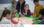 Купить «Teacher and collective of elementary age children draw together a board game», видеоролик № 33827375, снято 29 января 2020 г. (c) Яков Филимонов / Фотобанк Лори