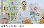 Smiling young pharmacist ready to assist at counter in pharmacy. Стоковое видео, видеограф Яков Филимонов / Фотобанк Лори