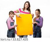 Купить «Мама и две дочки держат в руках оранжевую вывеску и указывают в нее», фото № 33827435, снято 15 мая 2020 г. (c) Иванов Алексей / Фотобанк Лори