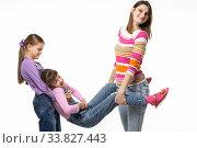 Купить «Мама и старшая дочка взяли за руки и ноги младшую дочку», фото № 33827443, снято 15 мая 2020 г. (c) Иванов Алексей / Фотобанк Лори