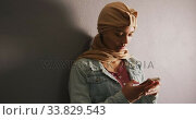 Asian female student wearing a beige hijab leaning against a wall and using a smartphone. Стоковое видео, агентство Wavebreak Media / Фотобанк Лори