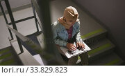 Asian female student wearing a beige hijab sitting on stairs and using a laptop. Стоковое видео, агентство Wavebreak Media / Фотобанк Лори