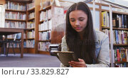 Asian female student sitting and using a tablet. Стоковое видео, агентство Wavebreak Media / Фотобанк Лори