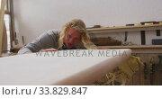 Купить «Caucasian male surfboard maker making a surfboard and preparing to polishing», видеоролик № 33829847, снято 6 марта 2020 г. (c) Wavebreak Media / Фотобанк Лори
