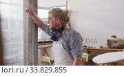 Купить «Caucasian male surfboard maker wearing a face mask and standing in his studio», видеоролик № 33829855, снято 6 марта 2020 г. (c) Wavebreak Media / Фотобанк Лори