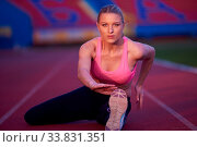 Купить «Young runner sporty woman relaxing and stretching on athletic race track», фото № 33831351, снято 7 августа 2020 г. (c) age Fotostock / Фотобанк Лори