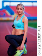 Купить «Young runner sporty woman relaxing and stretching on athletic race track», фото № 33831451, снято 7 августа 2020 г. (c) age Fotostock / Фотобанк Лори