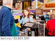 Купить «Mann als Kassierer und Frau als Kundin an der Supermarkt Kasse mit Obst», фото № 33831591, снято 5 июня 2020 г. (c) age Fotostock / Фотобанк Лори