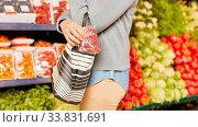 Купить «Frau steckt Erdbeeren in Handtasche bei Ladendiebstahl im Supermarkt», фото № 33831691, снято 5 июня 2020 г. (c) age Fotostock / Фотобанк Лори
