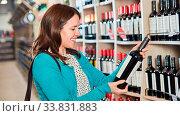 Купить «Junge Frau als Kundin im Supermarkt mit einer Flasche Rotwein in der Hand», фото № 33831883, снято 5 июня 2020 г. (c) age Fotostock / Фотобанк Лори