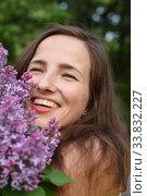 Купить «The face of a smiling young beautiful girl is large with a Bush of blooming lilac», фото № 33832227, снято 21 мая 2019 г. (c) Максим Мицун / Фотобанк Лори