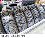 Winter vehicle tires stacked up for sale in the hypermarket. Редакционное фото, фотограф FotograFF / Фотобанк Лори