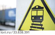 Купить «Close-up of a railway crossing, sign, freight train», видеоролик № 33838391, снято 24 мая 2020 г. (c) Mikhail Erguine / Фотобанк Лори