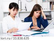 Two sad women looking documents at table in the office. Стоковое фото, фотограф Яков Филимонов / Фотобанк Лори