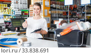 Купить «Portrait of happy woman seller at cash desk», фото № 33838691, снято 17 мая 2018 г. (c) Яков Филимонов / Фотобанк Лори