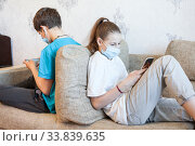 Брат и сестра играют в телефоне или общаются в сети, сидя на диване, маски на лицах. Стоковое фото, фотограф Кекяляйнен Андрей / Фотобанк Лори