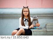 Купить «Child girl with plush toy and textbooks sits on the steps of the school stairs. Schoolgirl portrait. Selective focus.», фото № 33850643, снято 2 июня 2020 г. (c) easy Fotostock / Фотобанк Лори