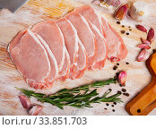 Купить «Preparation of raw pork fillet with rosemary and garlic on wooden board», фото № 33851703, снято 27 мая 2020 г. (c) Яков Филимонов / Фотобанк Лори