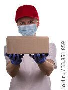 Купить «Woman courier in a red cap gives an order in a cardboard box isolated on a white», фото № 33851859, снято 7 мая 2020 г. (c) Сергей Молодиков / Фотобанк Лори