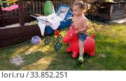 Купить «Calm little kid playing toy in backyard of country house in village», видеоролик № 33852251, снято 11 мая 2020 г. (c) Ekaterina Demidova / Фотобанк Лори
