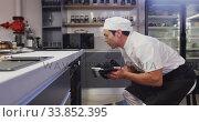 Купить «Mixed race male chef wearing chefs whites in a restaurant kitchen,taking food out of an oven», видеоролик № 33852395, снято 5 декабря 2019 г. (c) Wavebreak Media / Фотобанк Лори