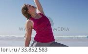 Купить «Caucasian woman doing yoga position on the beach and blue sky background», видеоролик № 33852583, снято 15 октября 2019 г. (c) Wavebreak Media / Фотобанк Лори