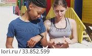 Купить «Multi-ethnic women using a phone on the beach and blue sky background», видеоролик № 33852599, снято 15 октября 2019 г. (c) Wavebreak Media / Фотобанк Лори