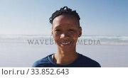 Купить «African American woman looking at camera and smiling on the beach and blue sky background», видеоролик № 33852643, снято 15 октября 2019 г. (c) Wavebreak Media / Фотобанк Лори