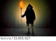 Купить «Ugly scary man with burning flambeau walking in an empty space», фото № 33855927, снято 27 мая 2020 г. (c) easy Fotostock / Фотобанк Лори