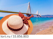 Women's wide-brimmed straw hat with bow. Beautiful sandy beach on the shores of the Gulf of Corinth. Greece. White cable-stayed bridge. The concept of sea summer recreation. Стоковое фото, фотограф Zoonar.com/kavram / easy Fotostock / Фотобанк Лори