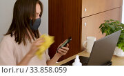 Купить «Woman in mask disinfection smartphone», видеоролик № 33858059, снято 26 мая 2020 г. (c) Ekaterina Demidova / Фотобанк Лори