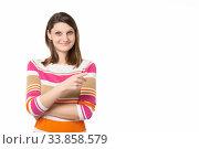 Купить «Девушка с очаровательной улыбкой указывает пальцем на пустое место, белый фон», фото № 33858579, снято 15 мая 2020 г. (c) Иванов Алексей / Фотобанк Лори