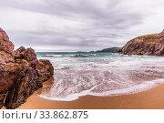 Купить «View from small hidden beach towards rocks, sea waves, cliffs and islands in the distance, moody stormy clouds», фото № 33862875, снято 2 июня 2020 г. (c) easy Fotostock / Фотобанк Лори