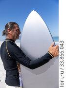 Купить «Senior Caucasian man holding a surfboard at the beach.», фото № 33866043, снято 25 февраля 2020 г. (c) Wavebreak Media / Фотобанк Лори