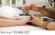 Купить «Beautician Grinds The Nail Bar For a Manicure In the Beauty Salon. Finger Nail Treatment, Grinding And Polishing. Manicurist Hands Make Female Manicure In The Nail Salon», видеоролик № 33866327, снято 28 мая 2020 г. (c) Алексей Кузнецов / Фотобанк Лори