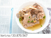 Slow Cooker Pork Bone Broth, it's simmered for many hours to extract as much nutrients from it. The long cooking time breaks down bone to release vitamins, collagen, nutrients are good for us. Стоковое фото, фотограф Zoonar.com/Pinrath Phanpradith / easy Fotostock / Фотобанк Лори