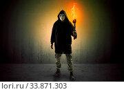Купить «Ugly scary man with burning flambeau walking in an empty space», фото № 33871303, снято 30 мая 2020 г. (c) easy Fotostock / Фотобанк Лори