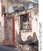 Купить «An old ruined house partly collapsed on a sloping street with a blocked up door crumbling walls and fading red painted windows with closed shutters», фото № 33871647, снято 4 июня 2020 г. (c) easy Fotostock / Фотобанк Лори