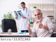 Купить «Young male doctor and old patient in antismoking concept», фото № 33872843, снято 9 сентября 2019 г. (c) Elnur / Фотобанк Лори