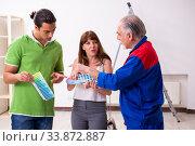 Купить «Young couple and old contractor in home renovation concept», фото № 33872887, снято 2 сентября 2019 г. (c) Elnur / Фотобанк Лори