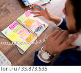 Купить «Young handsome employee planning his work activity», фото № 33873535, снято 1 августа 2018 г. (c) Elnur / Фотобанк Лори