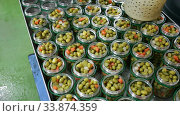 Купить «Hands of African worker filling glass jars with pickled green olives in packaging shop at factory», видеоролик № 33874359, снято 21 ноября 2019 г. (c) Яков Филимонов / Фотобанк Лори